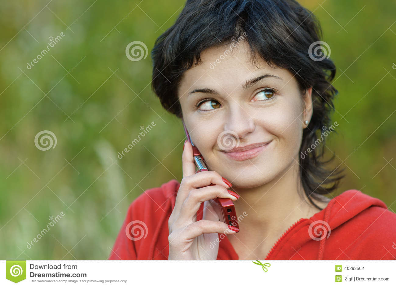 Девушка в парке говорит телефоном