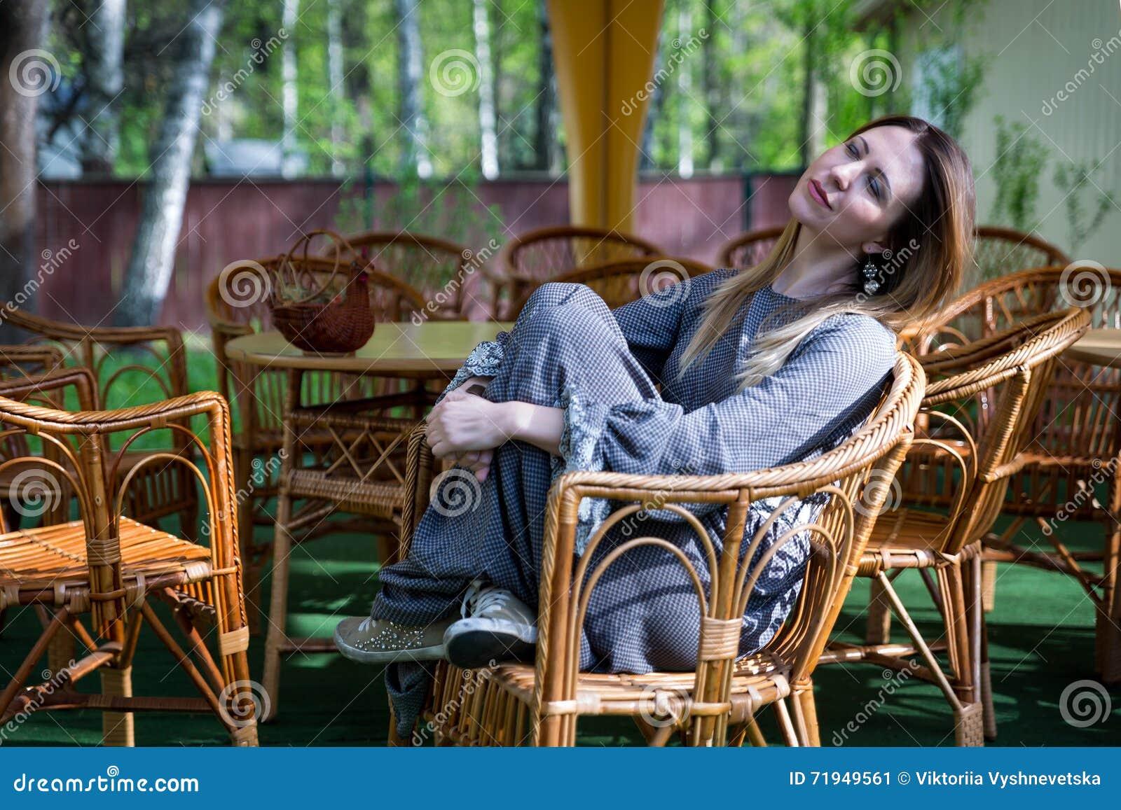 Девушка в плетеном стуле в солнце позднего вечера
