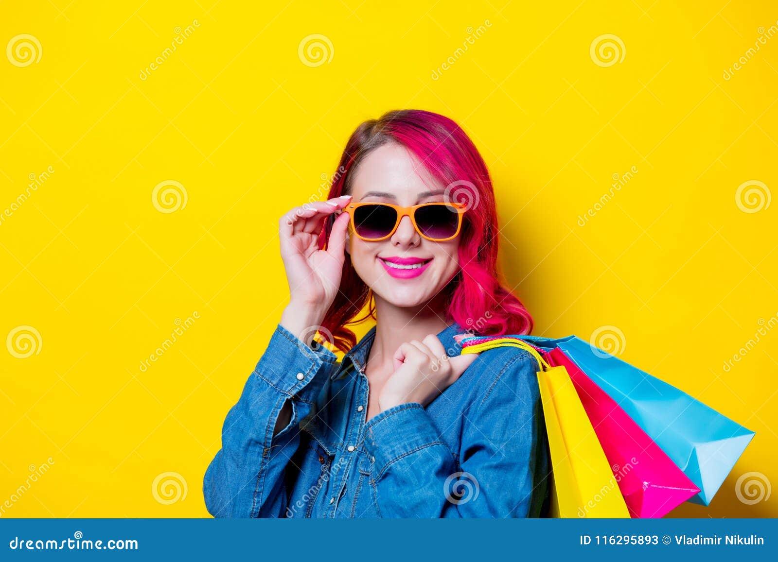 Девушка в солнечных очках держащ покрашенные хозяйственные сумки ... f2a08482af0