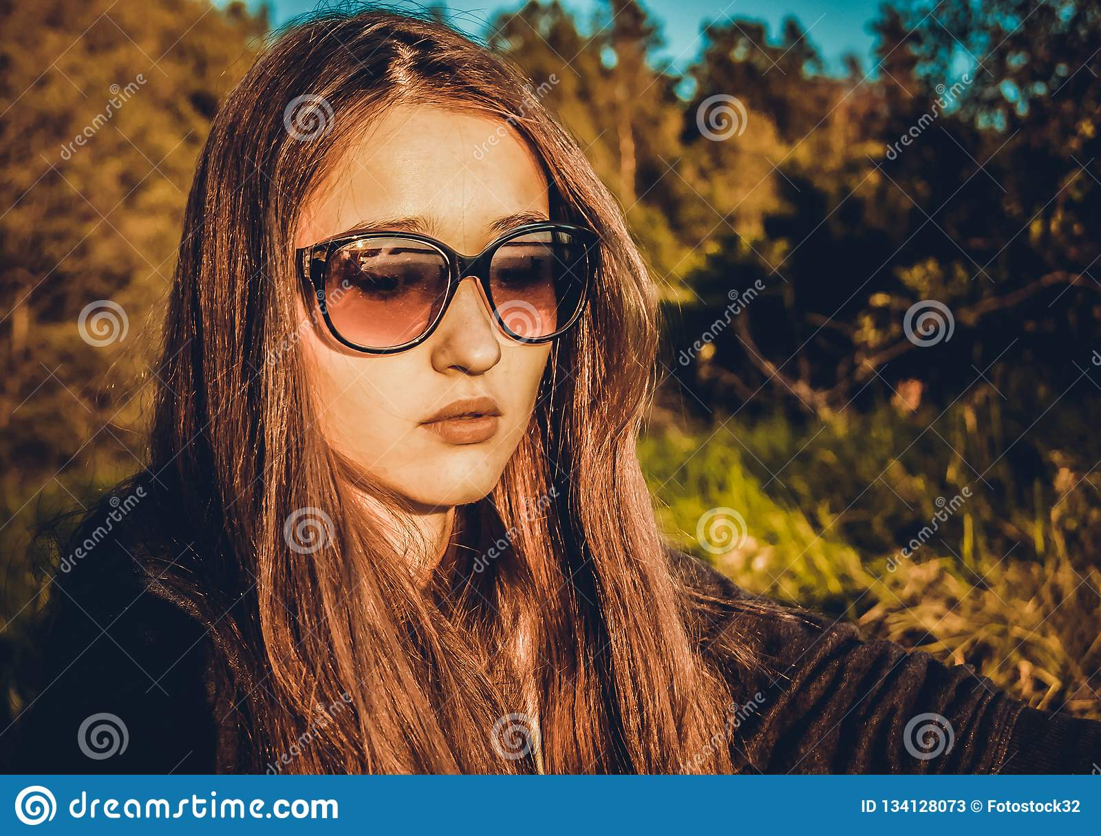 Девушка в стеклах на предпосылке природы
