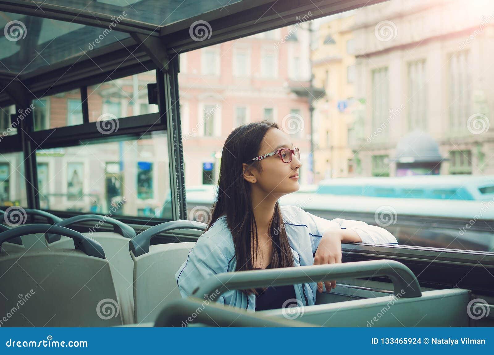 Девушка в стеклах сидит внутри туристического автобуса и взглядов в камеру и смотрит вне окно