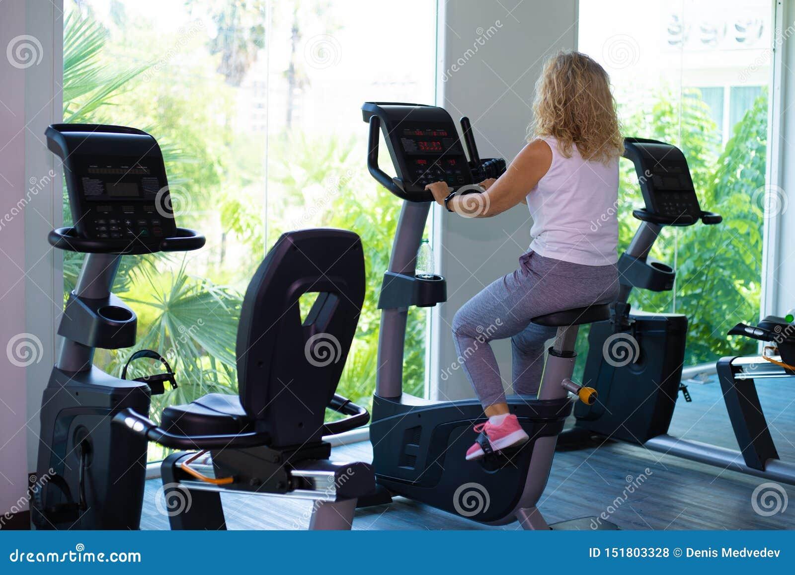 Девушка в черной носке спорта энергично работает на велотренажере