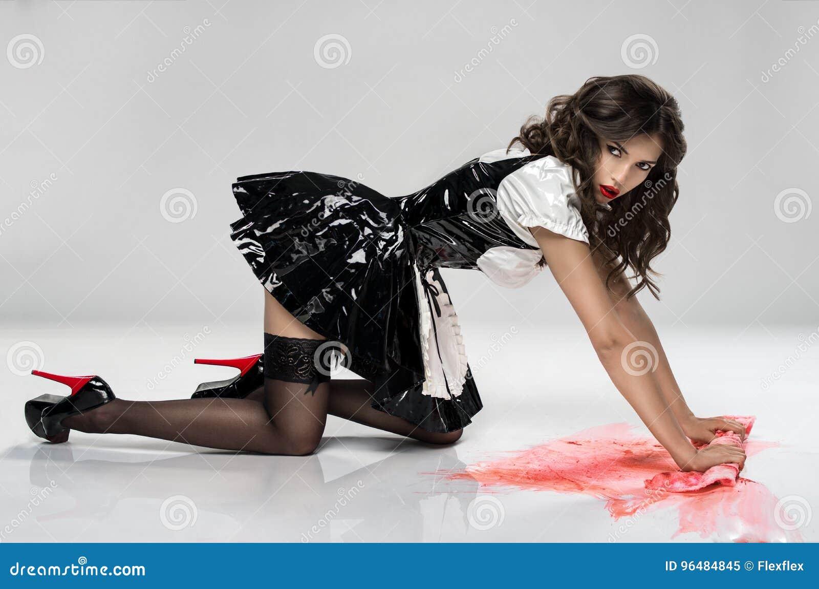 Девушка в черном платье латекса извлекает кровь