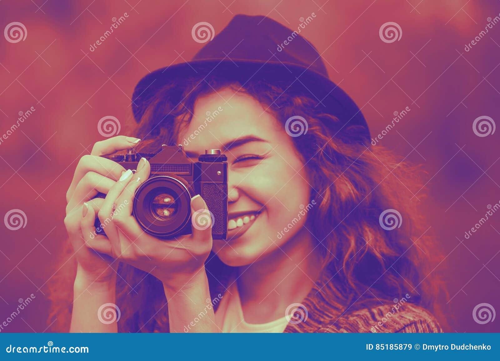 Девушка в шляпе усмехаясь и фотографируя природу