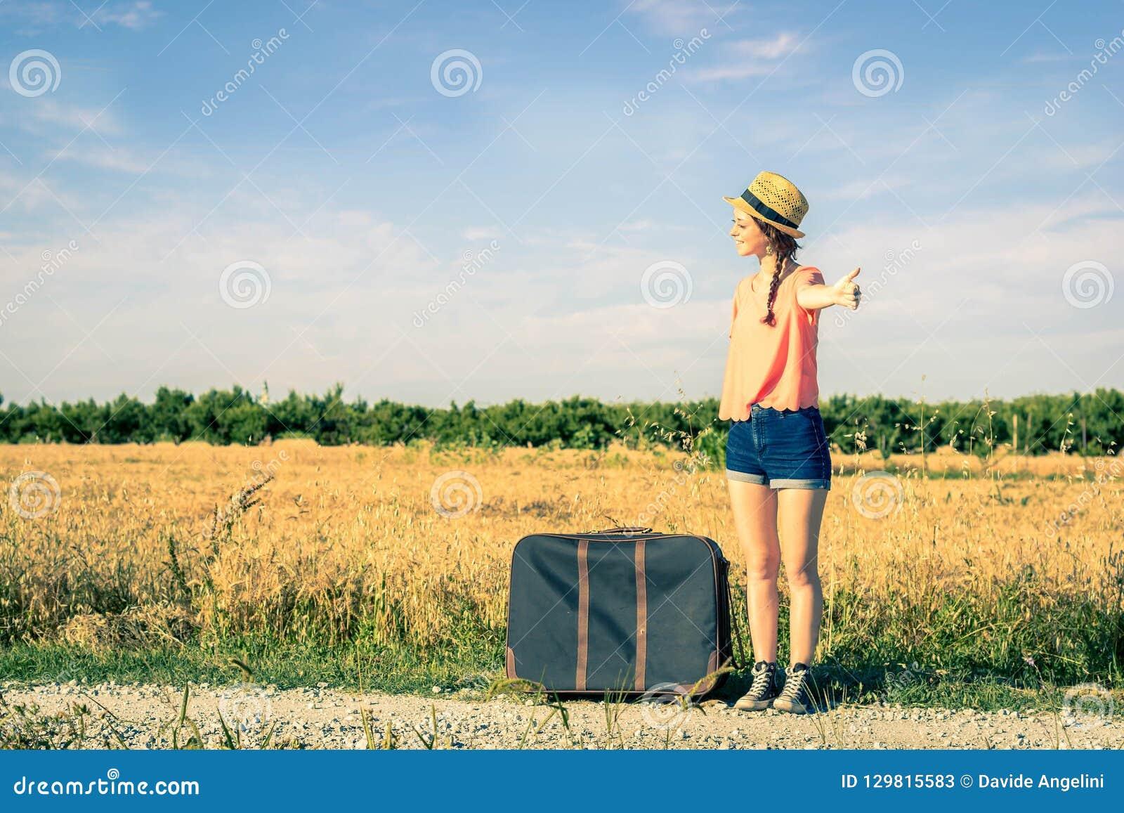 Девушка делая путешествовать автостопом на дороге