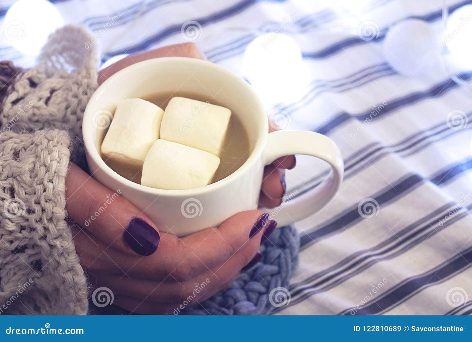 Девушка держит кофе с зефиром