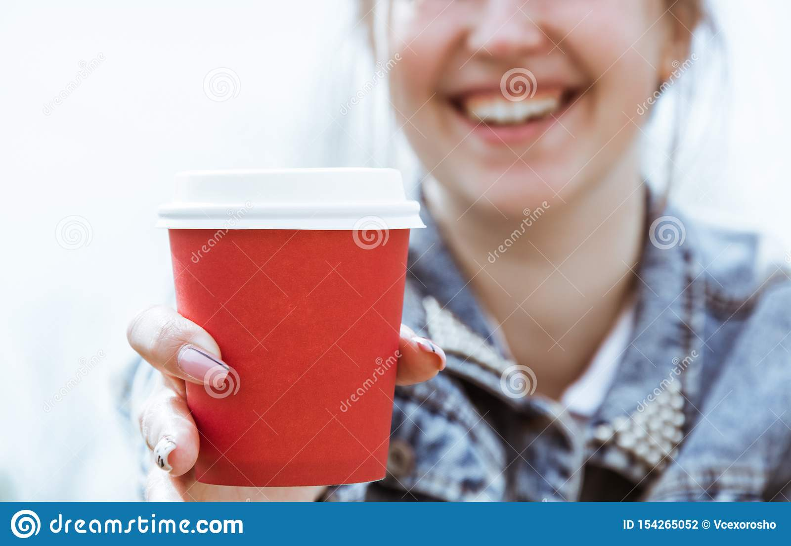 Девушка держит красный бумажный стаканчик кофе Стекло конца-вверх кофе в руке