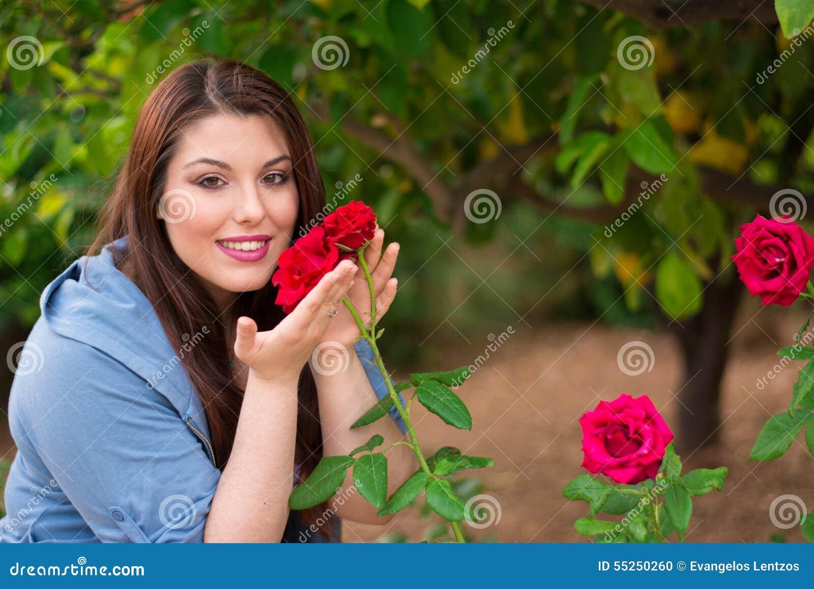 Девушка держа красные розы