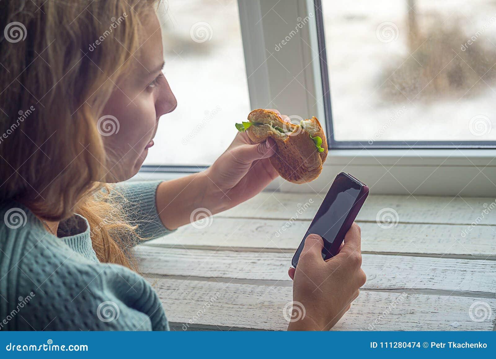 Девушка есть бургер и смотря телефон