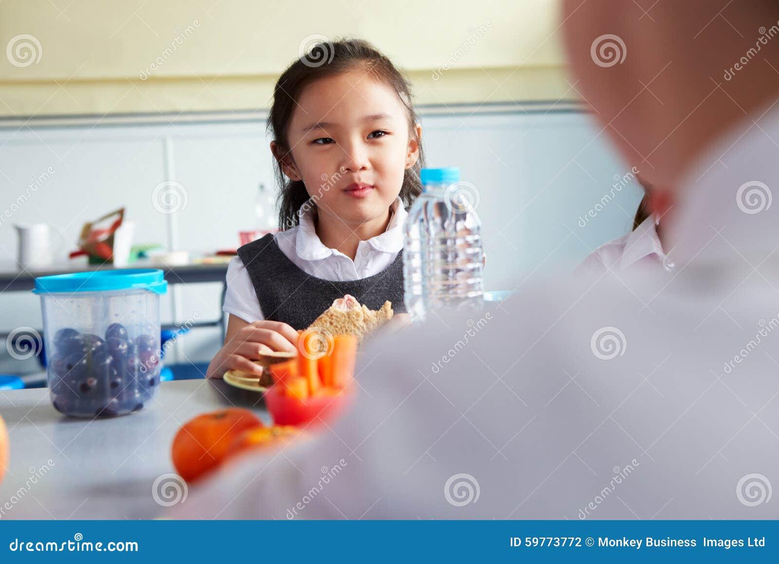 Девушка есть здоровый упакованный обед в школьном кафетерии