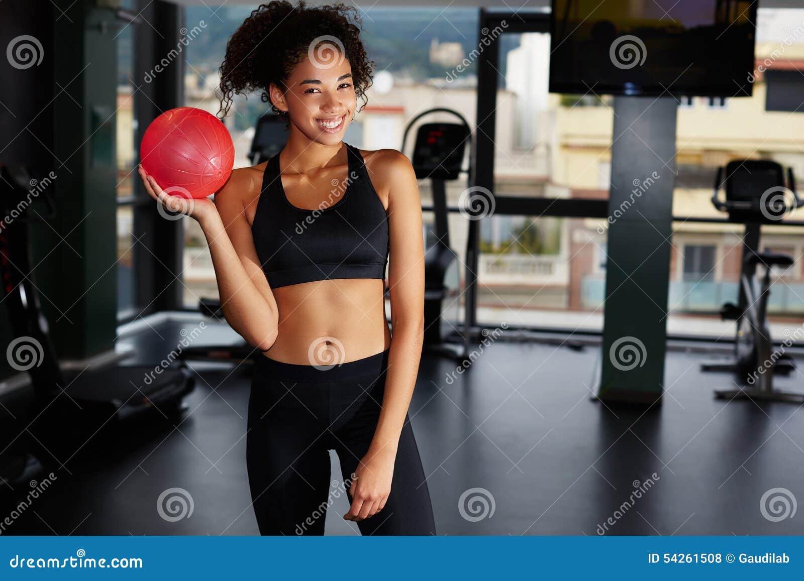 Девушка детенышей подходящая с тонизировать шарик на фитнес-клубе