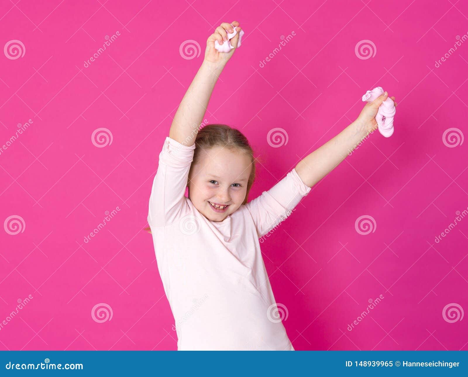 Девушка играет с желтым шламом перед розовой предпосылкой