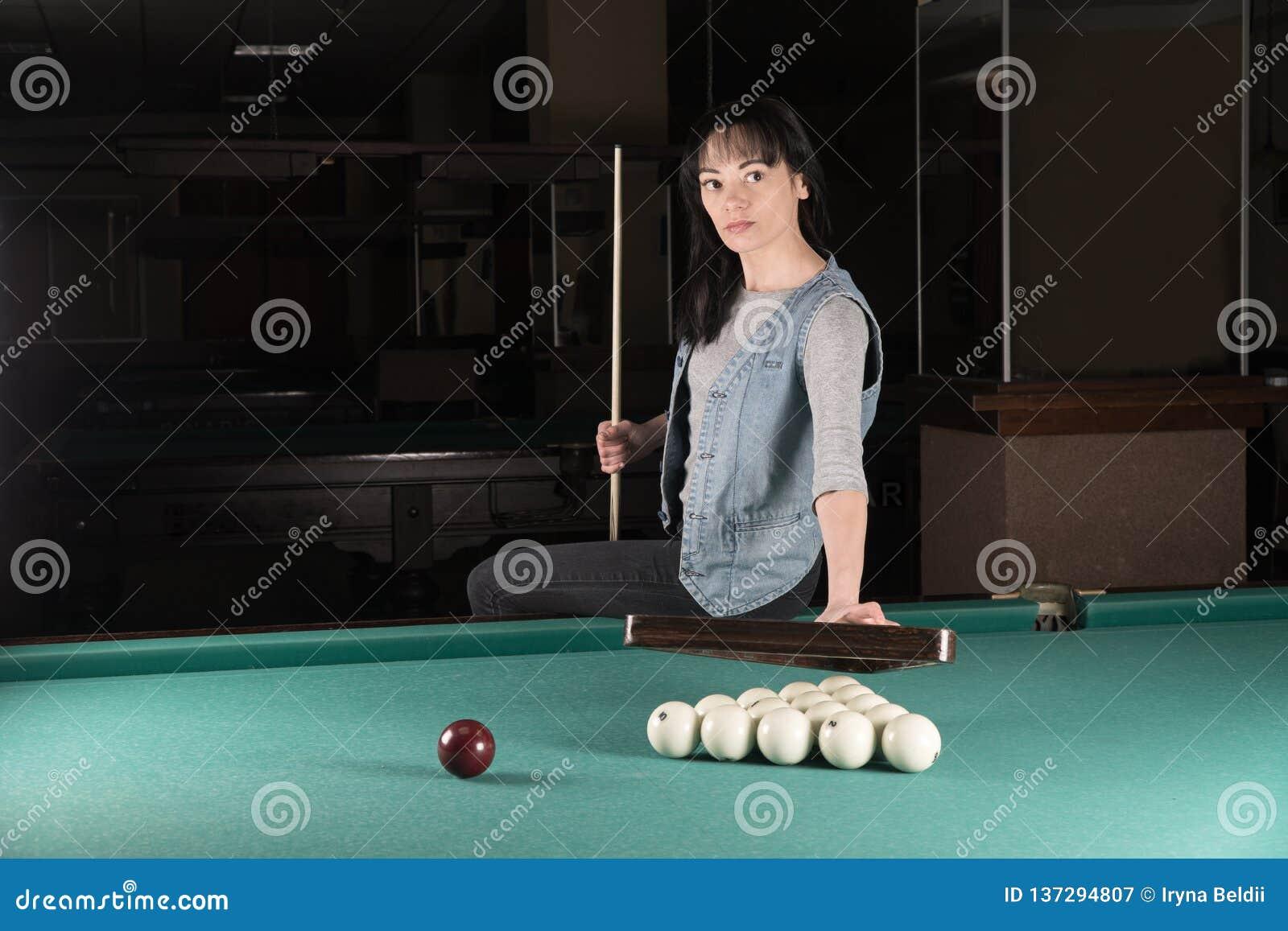 Девушка играя биллиарды женщина держа ручку сигнала