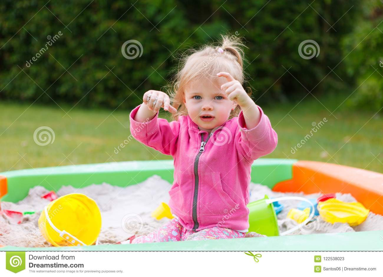 Девушка играя в коробке песка