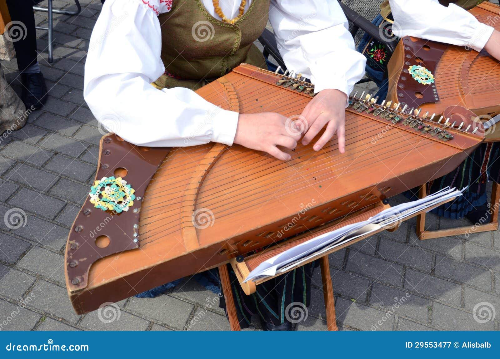 Девушка играя с аппаратурой ethnographic строки музыкальной