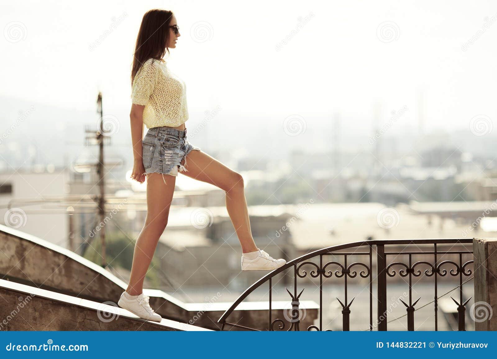 Девушка идет на крышу Город на предпосылке