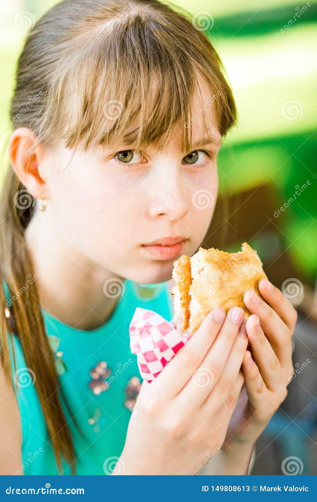 Девушка идет съесть гамбургер
