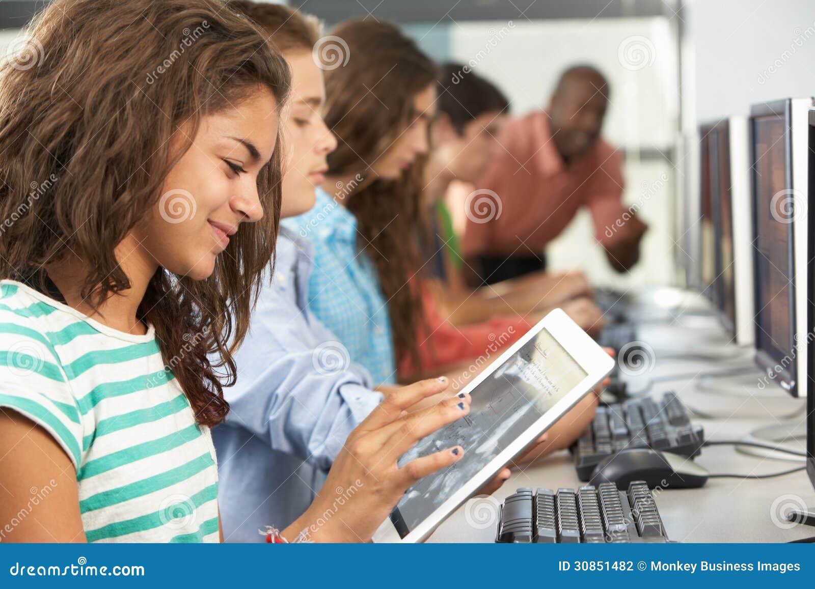 Девушка используя таблетку цифров в классе компьютера
