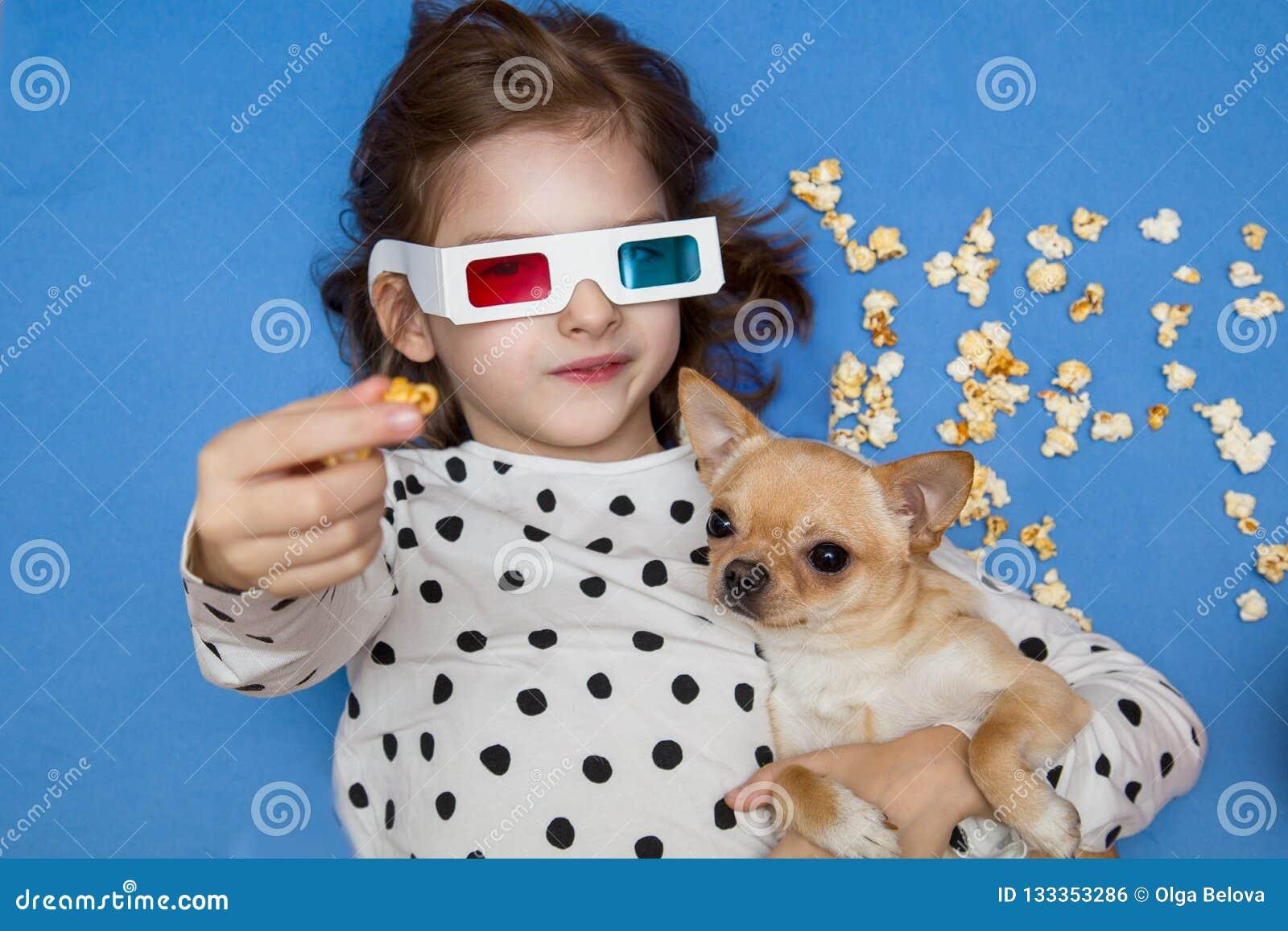 Девушка и маленькая собака смотря фильм в стеклах 3D с попкорном