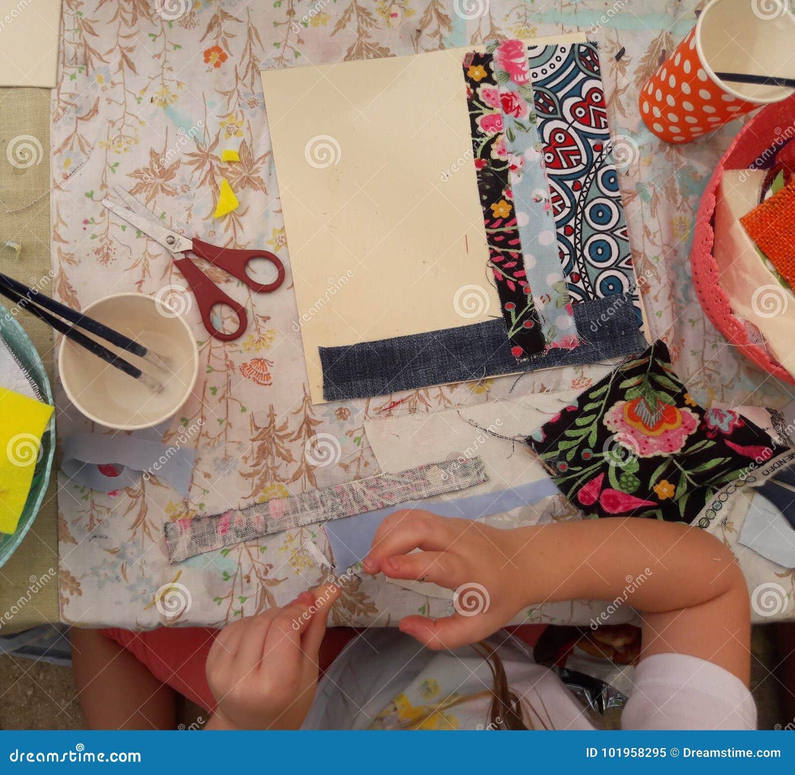 Девушка клеит и режет ткань в изображение