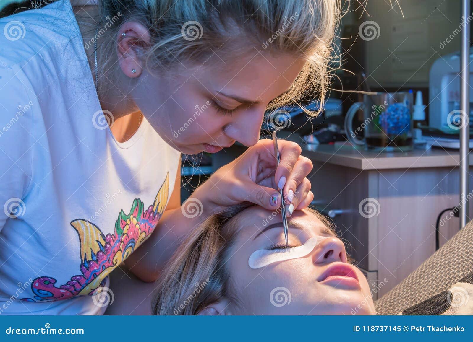 Девушка клеит ресницы