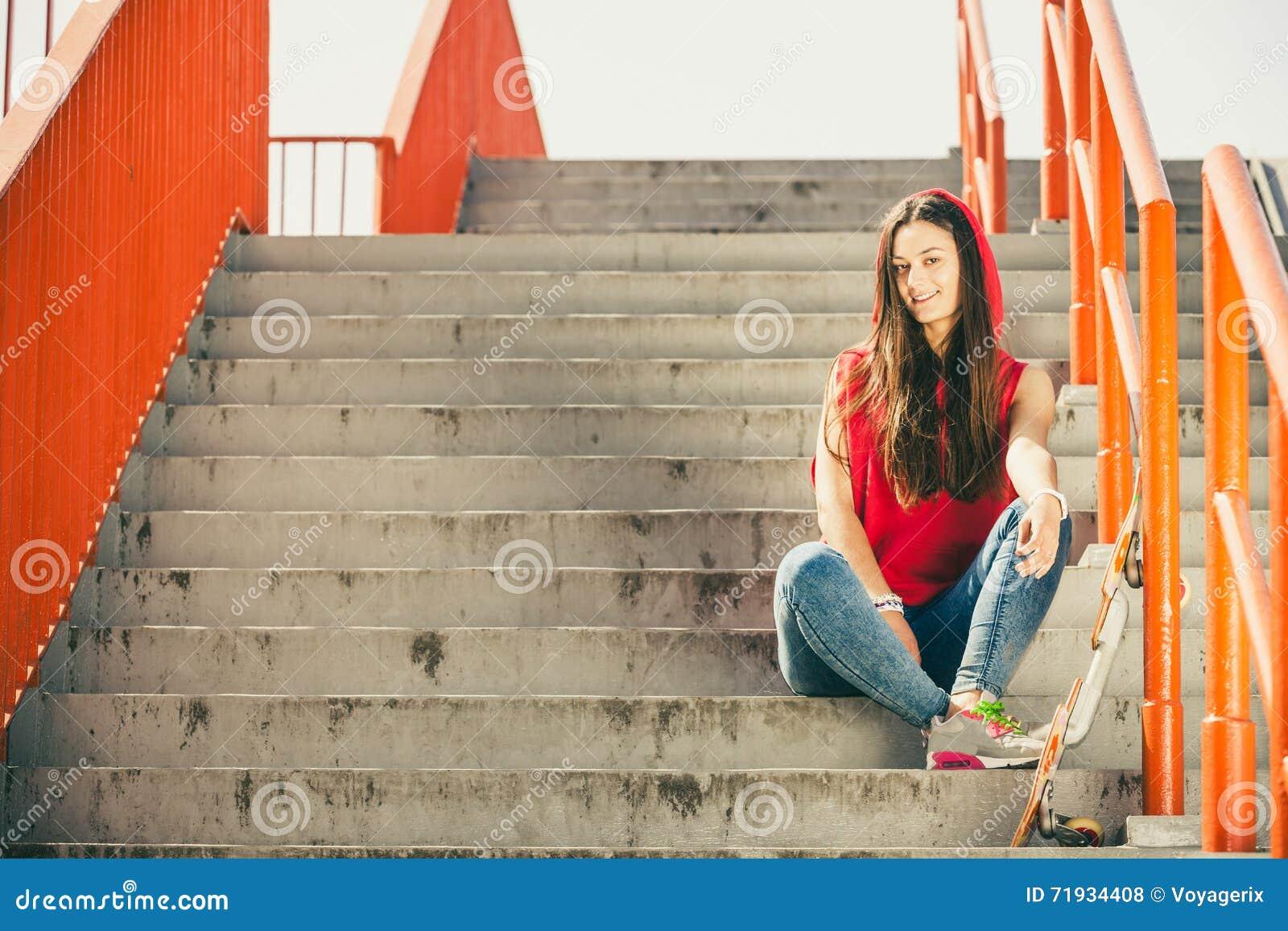 Девушка конька на лестницах с скейтбордом