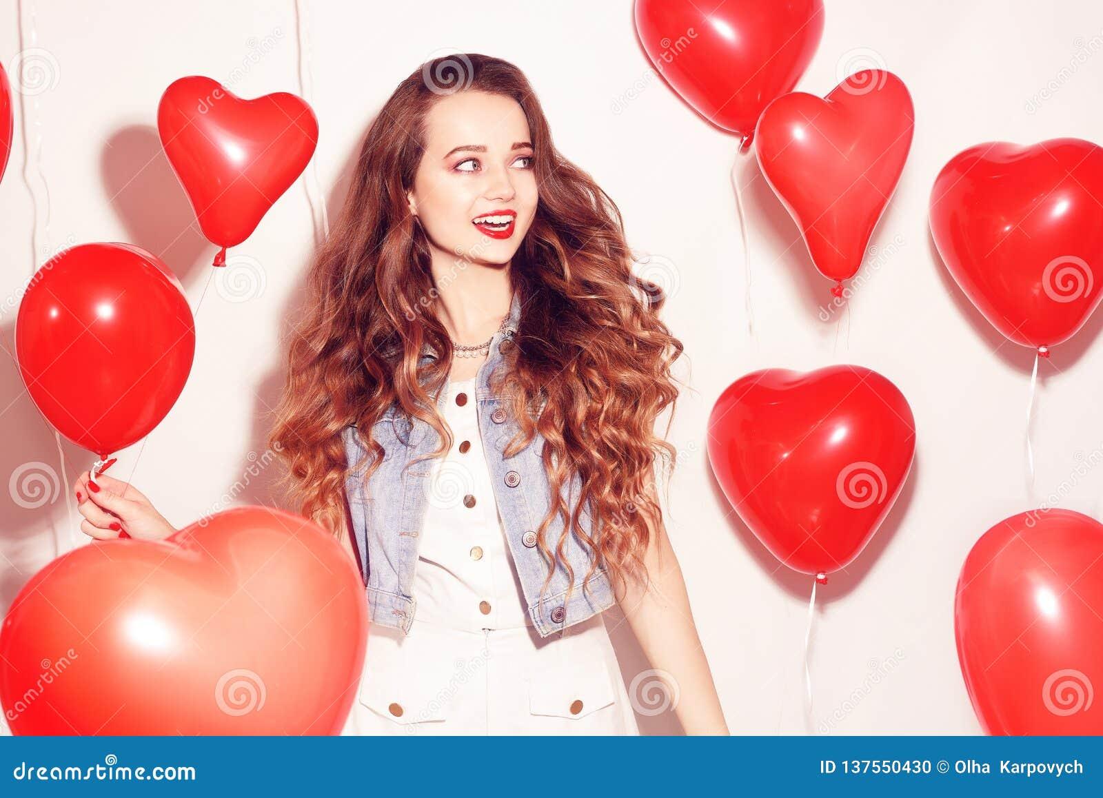 Девушка красоты Валентайн с красными воздушными шарами смеясь, на белой предпосылке красивейшие счастливые детеныши женщины День