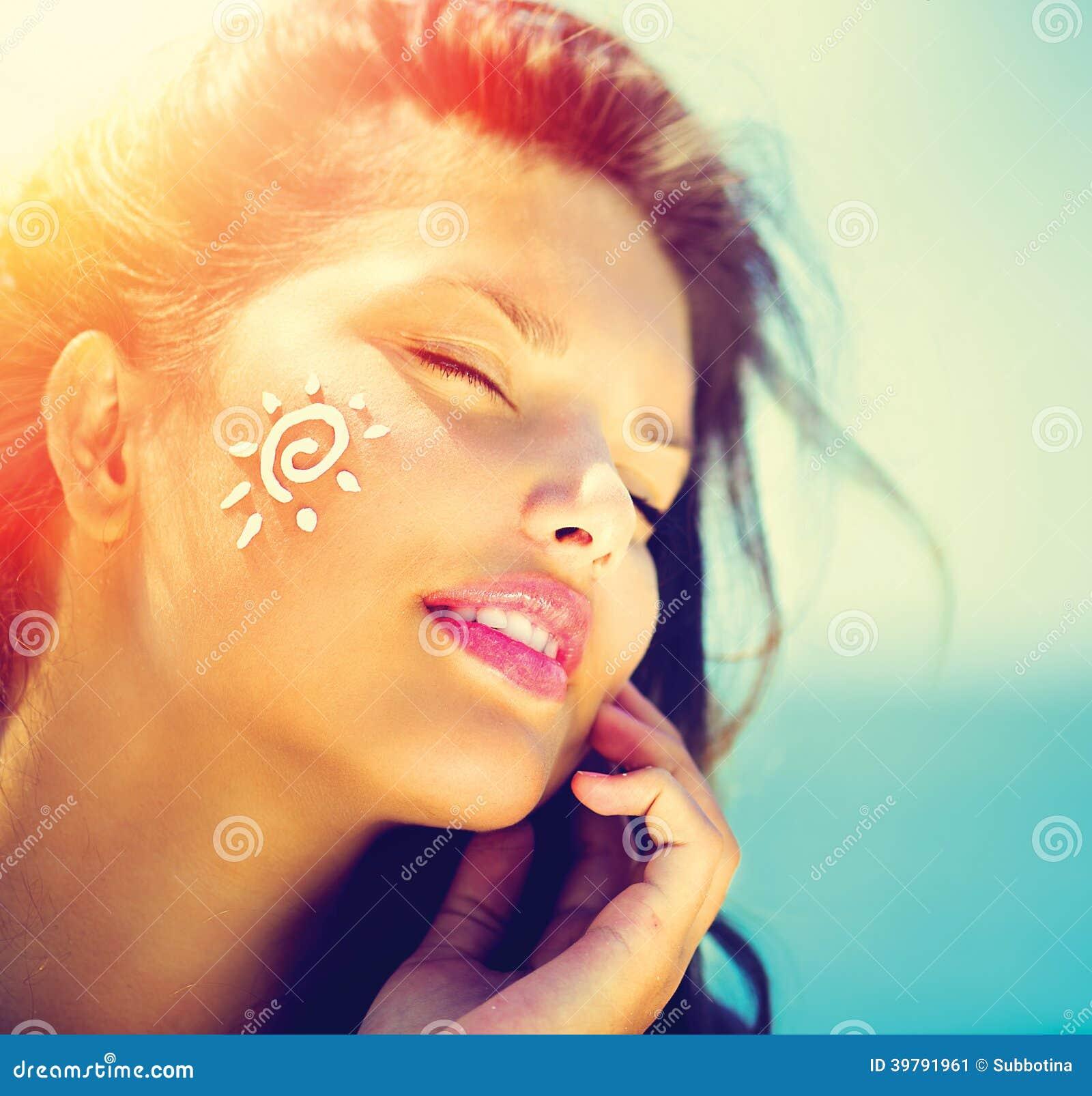 Девушка красоты прикладывая сливк suntan
