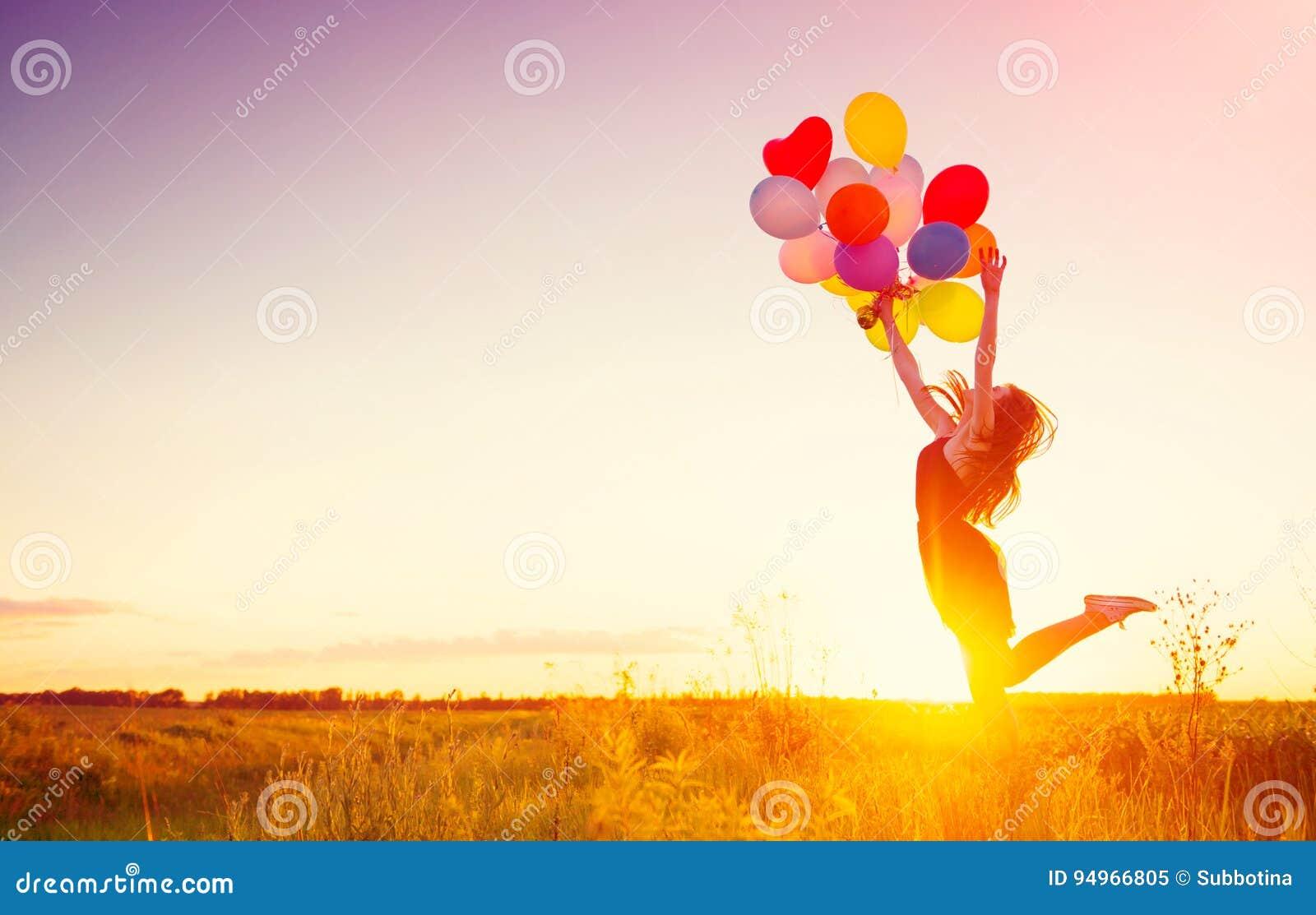 Девушка красоты с красочными воздушными шарами над небом захода солнца