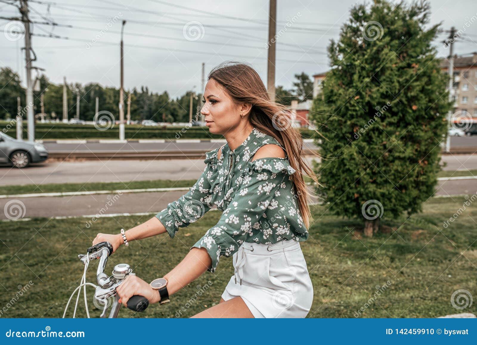 Девушка летом в городе, ехать велосипед, против фона деревьев и зеленых автомобилей В зеленых свитере и белизне