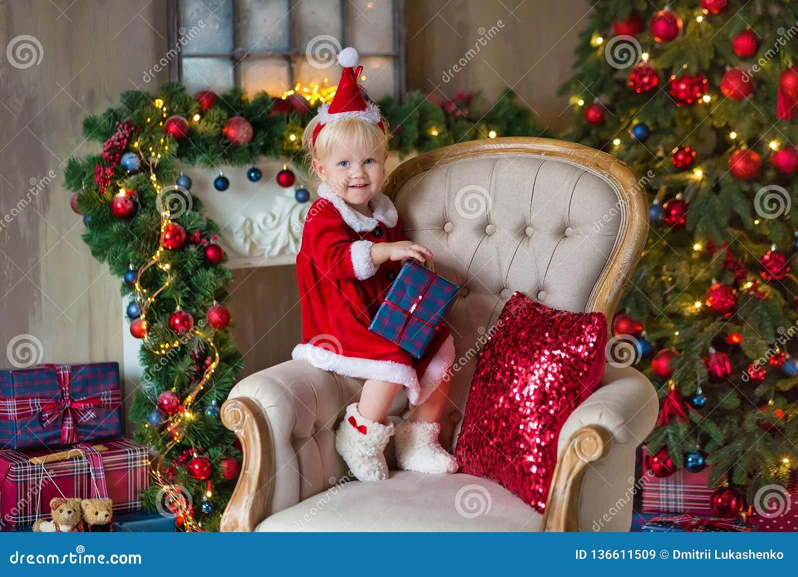Девушка маленького ребенка веселого рождества и счастливых праздников милая украшает рождественскую елку внутри помещения