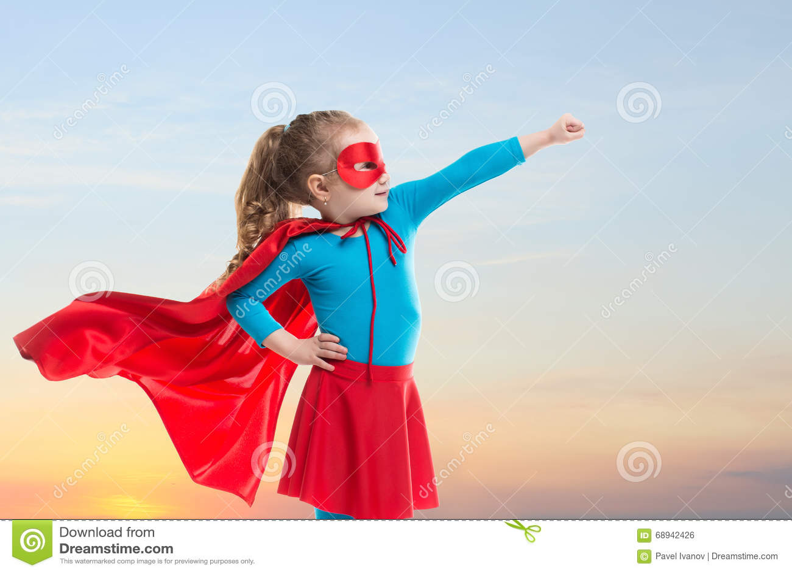 Девушка маленького ребенка играет супергероя Ребенок на предпосылке неба захода солнца