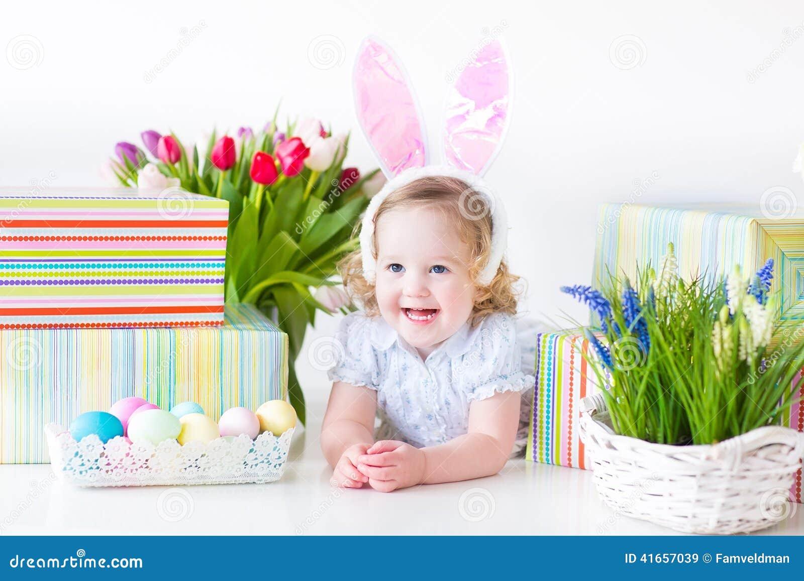 Девушка малыша в ушах зайчика играя с красочным f