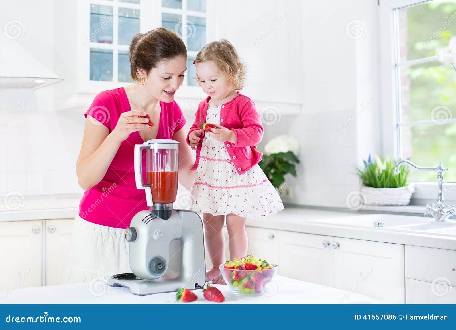 Девушка малыша и ее мать делая свежую клубнику