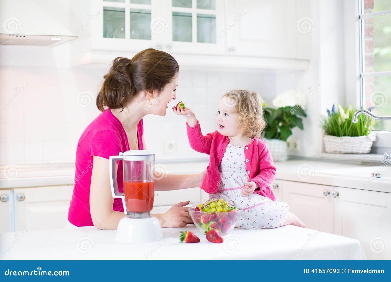 Девушка малыша и прелестная мать делая свежую клубнику