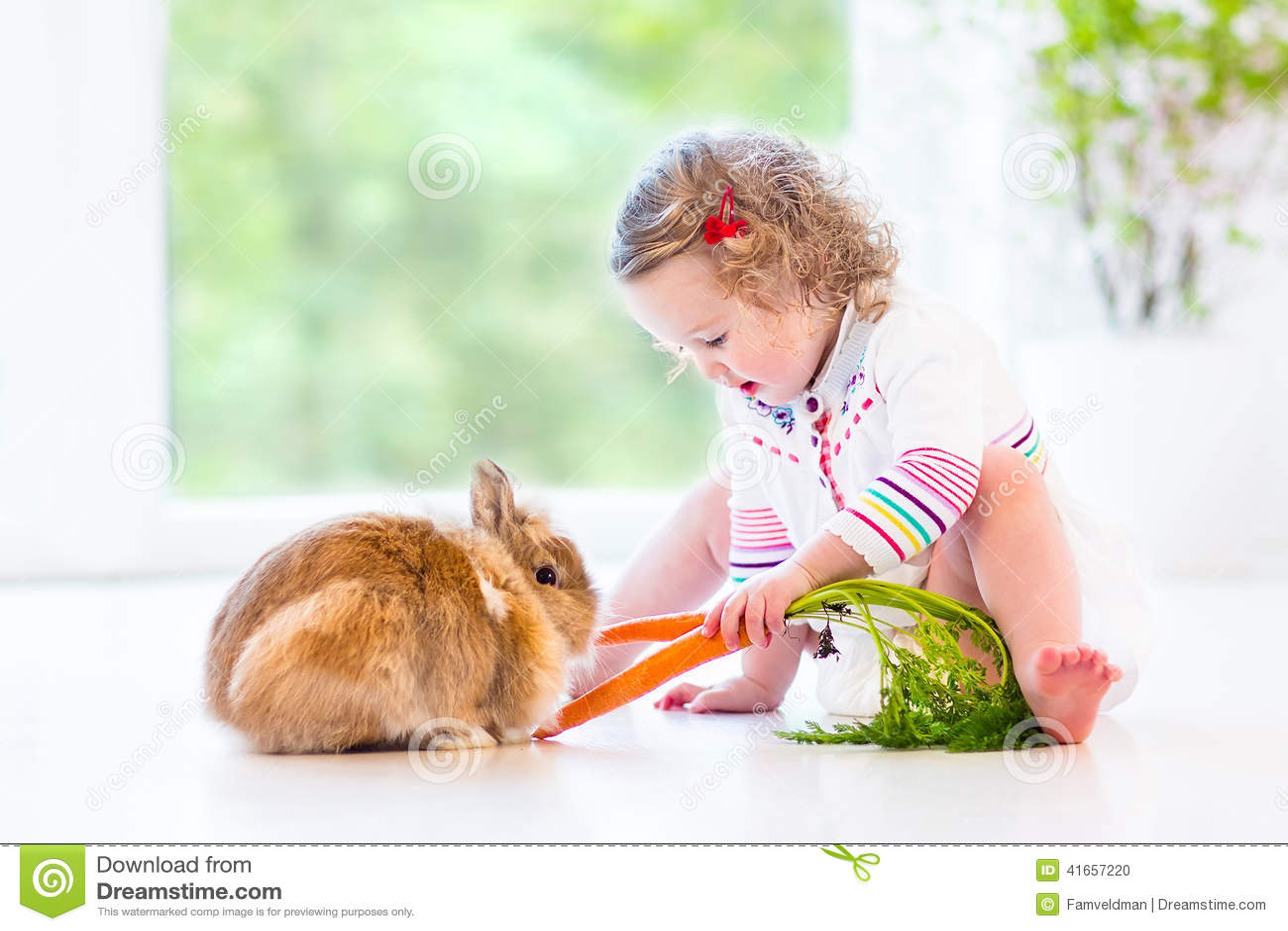 Девушка малыша при вьющиеся волосы играя с реальным зайчиком
