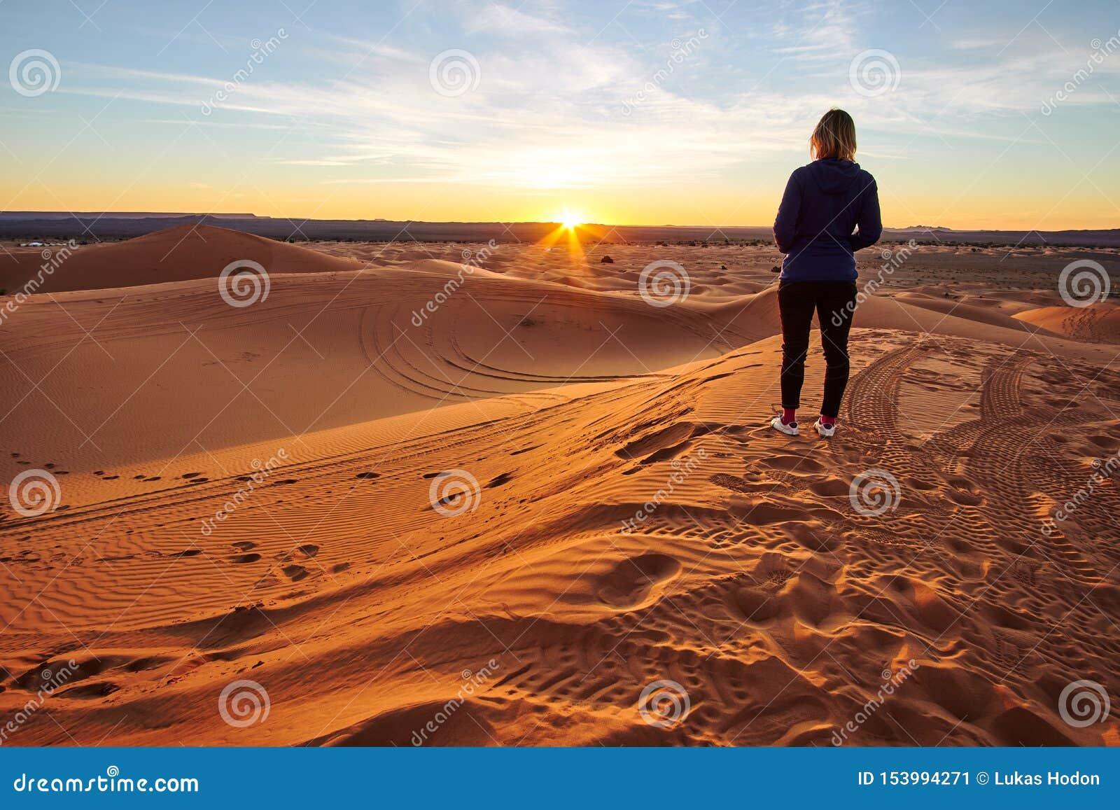 Девушка наблюдая восход солнца на песчанной дюне в пустыне Сахары