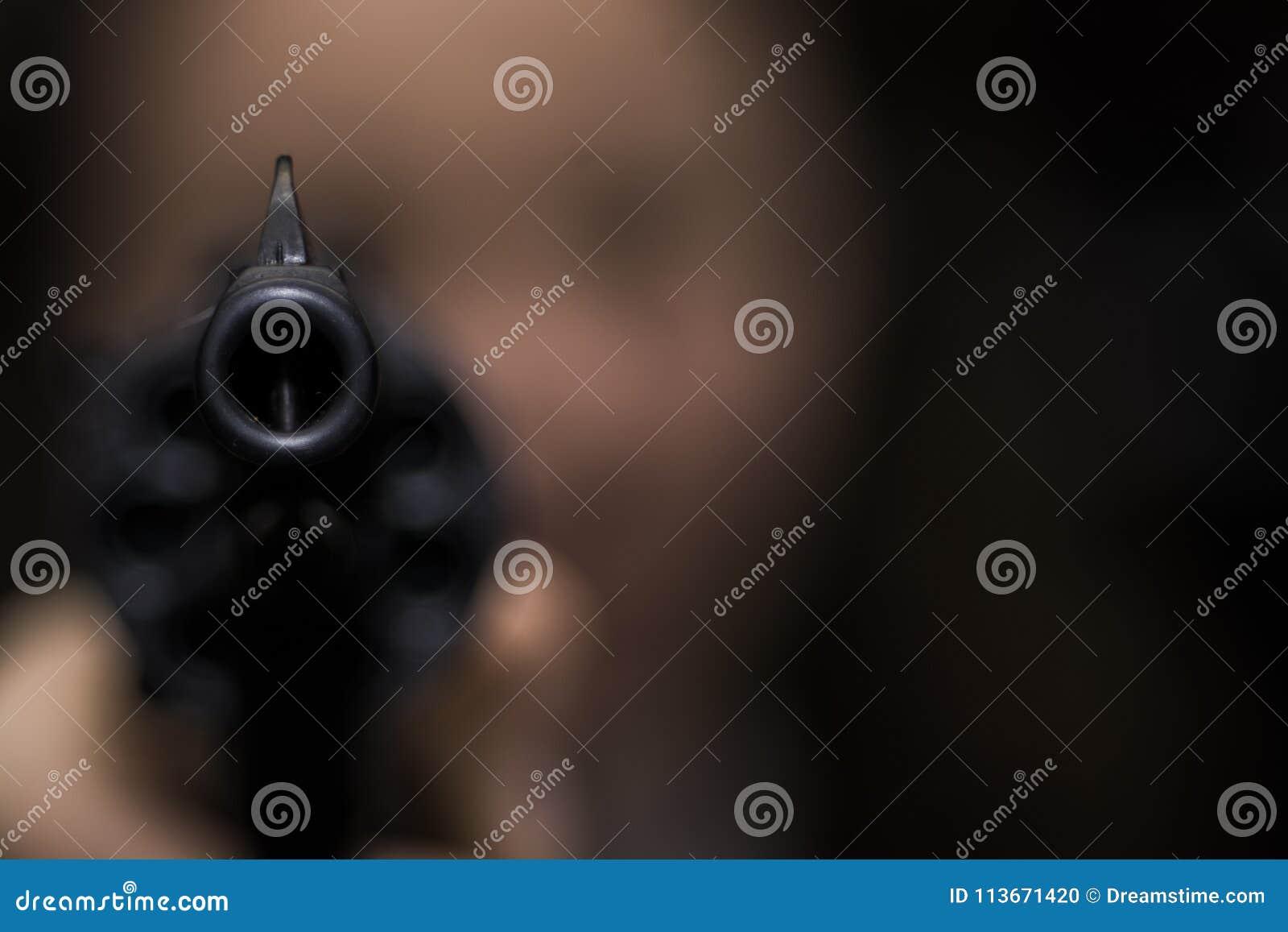 Девушка направляет от револьвера