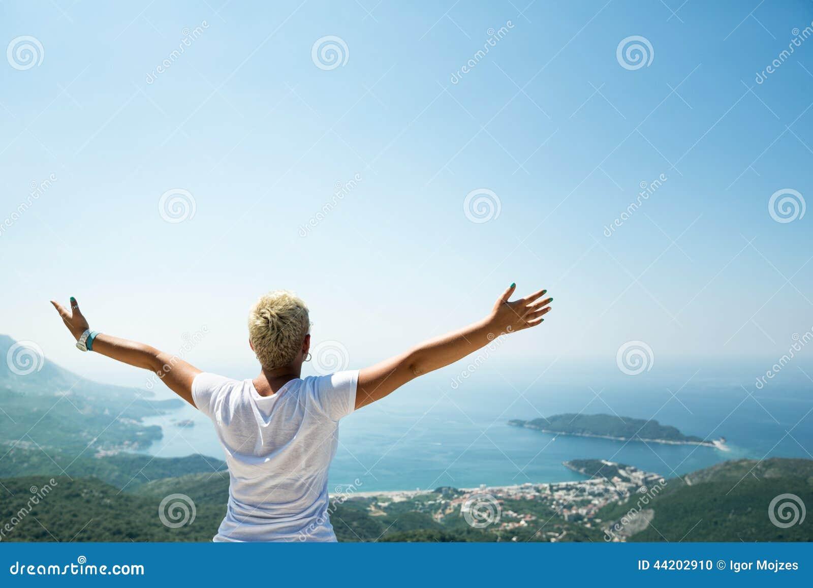 Девушка наслаждаясь в природе с поднятыми вверх руками