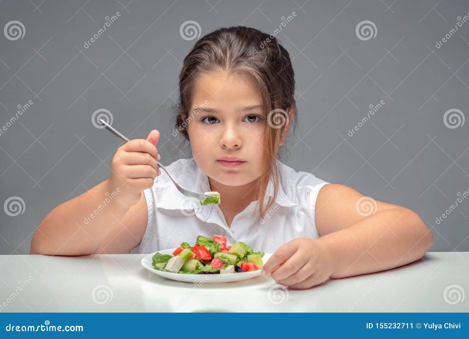 Девушка на таблице есть салат, полный ребенка