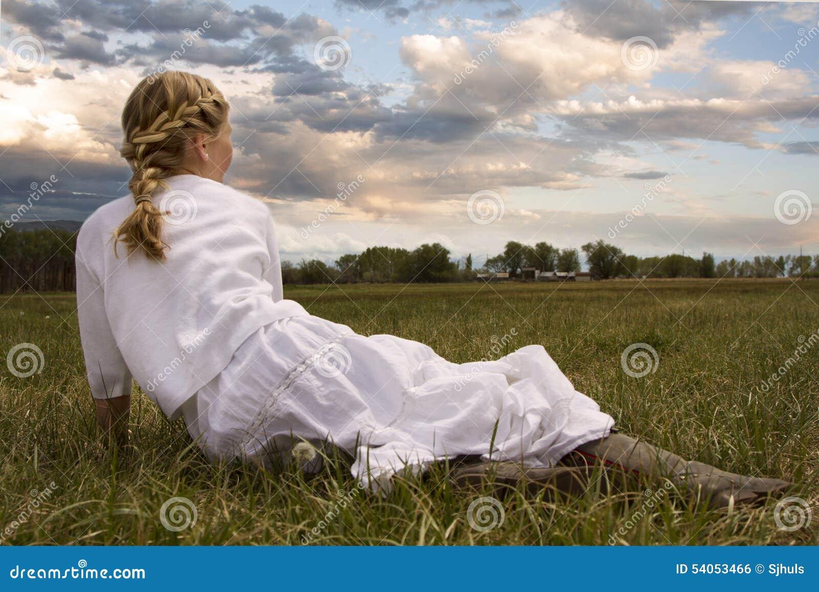 Девушка нося платье сидя в выгоне