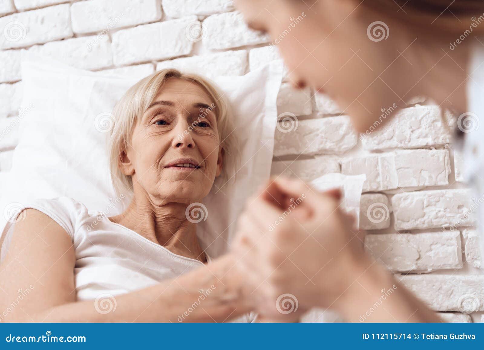 Девушка нянчит пожилую женщину дома Они держат руки, счастливые