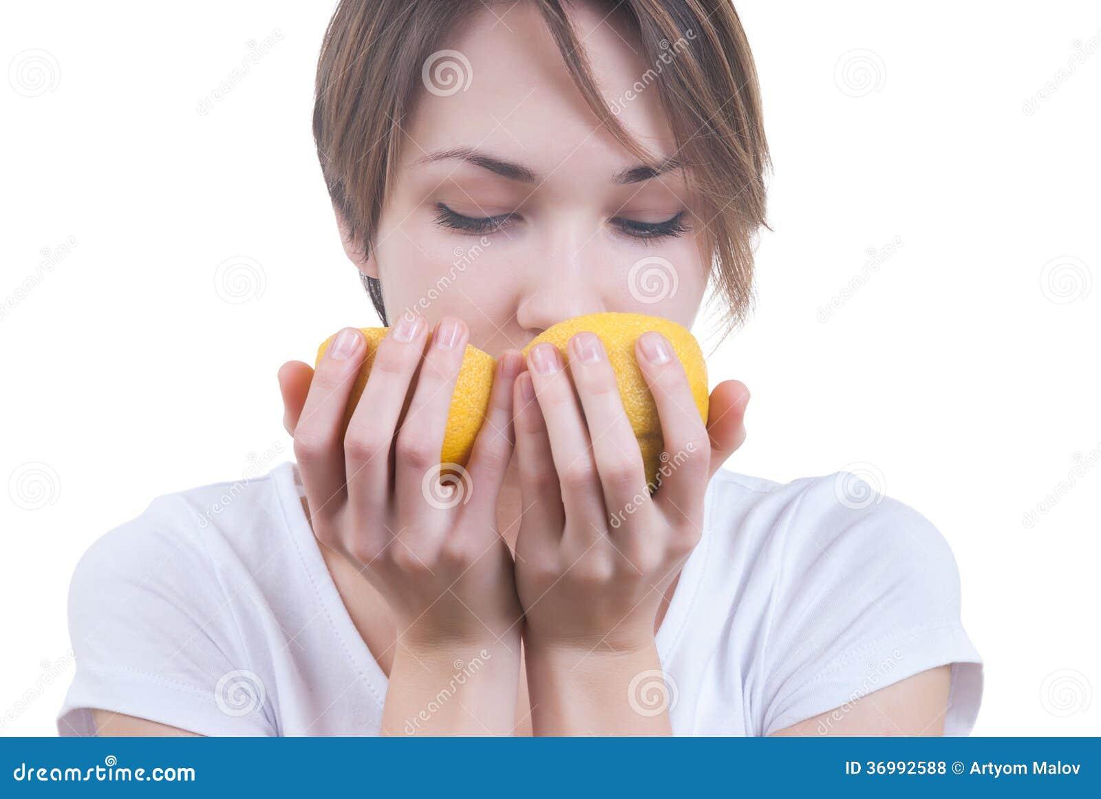 Девушка обнюхивая 2 части лимона