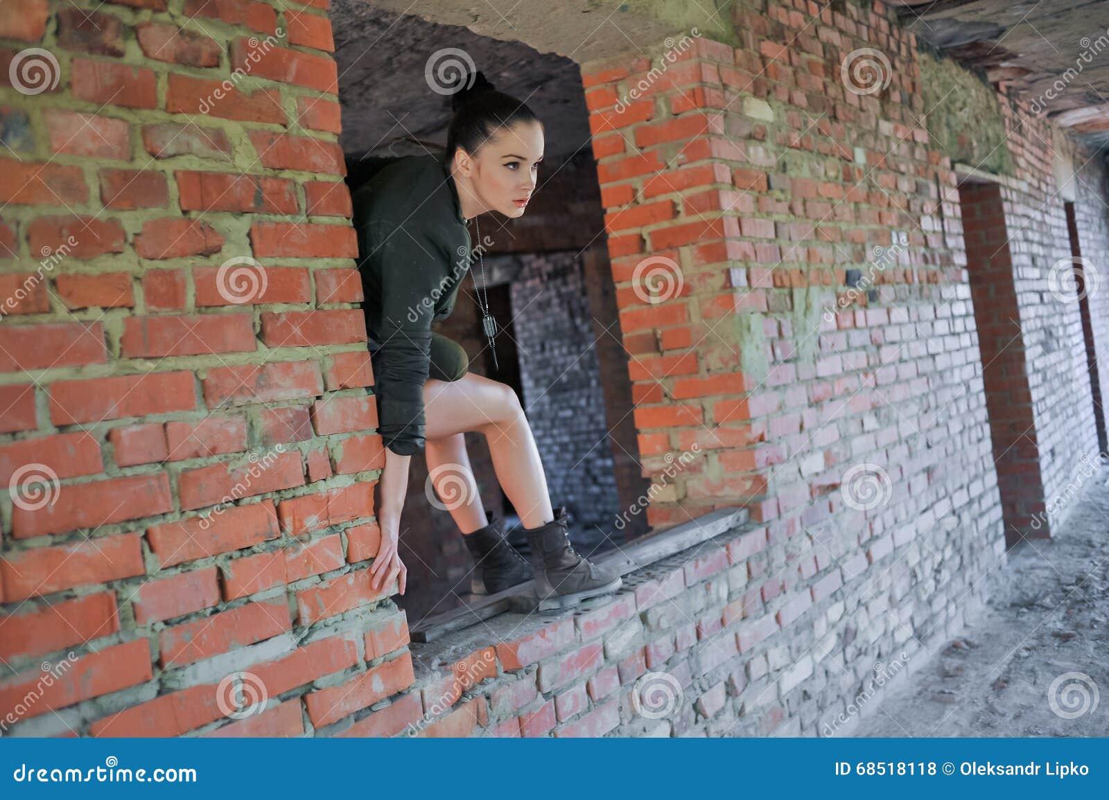 Девушка около кирпичной стены в стиле войск