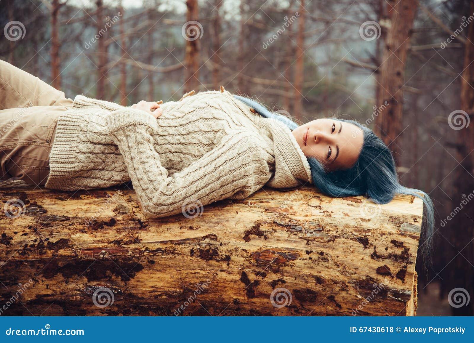 Девушка отдыхая на стволе дерева