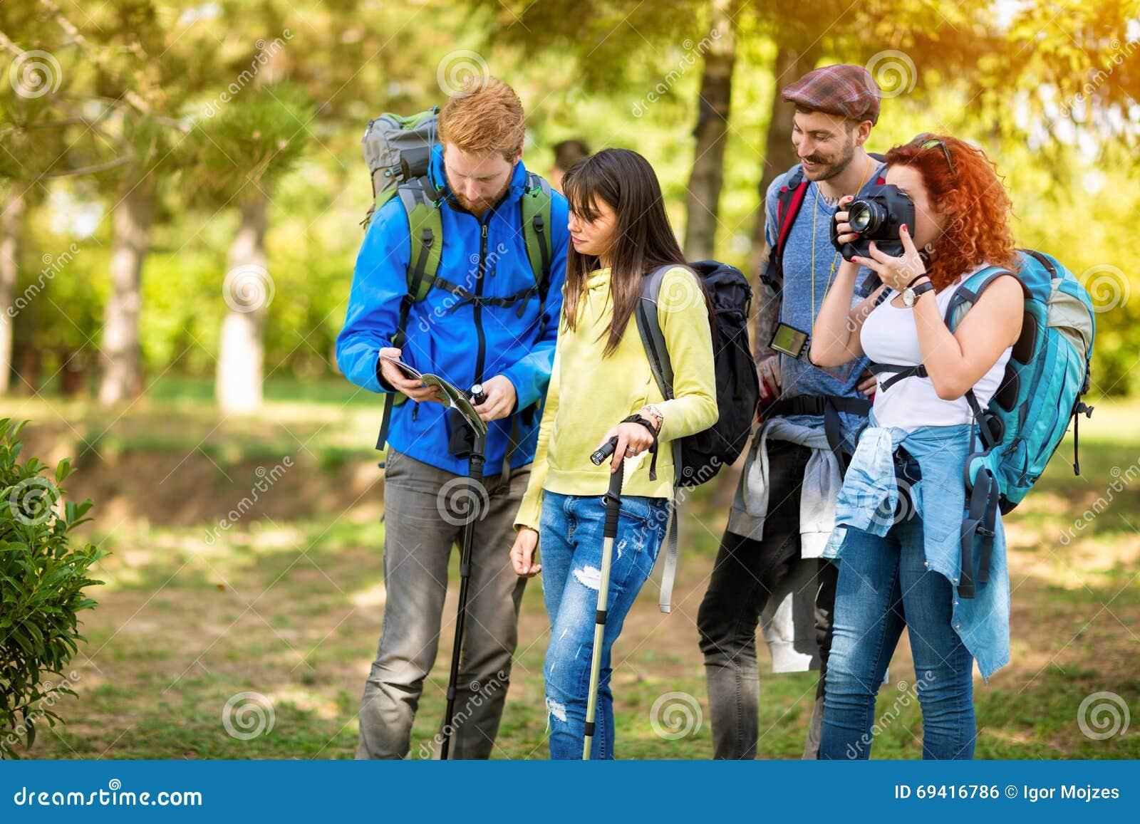 Девушка от hikers собирает фотографировать до тех пор пока другие не будут смотреть карту