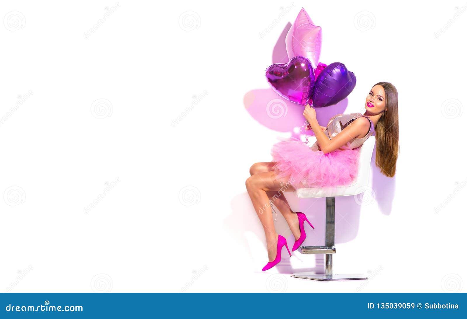 Девушка партии фотомодели красоты с сердцем сформировала представлять воздушных шаров, сидя на стуле День рождения, день Святого