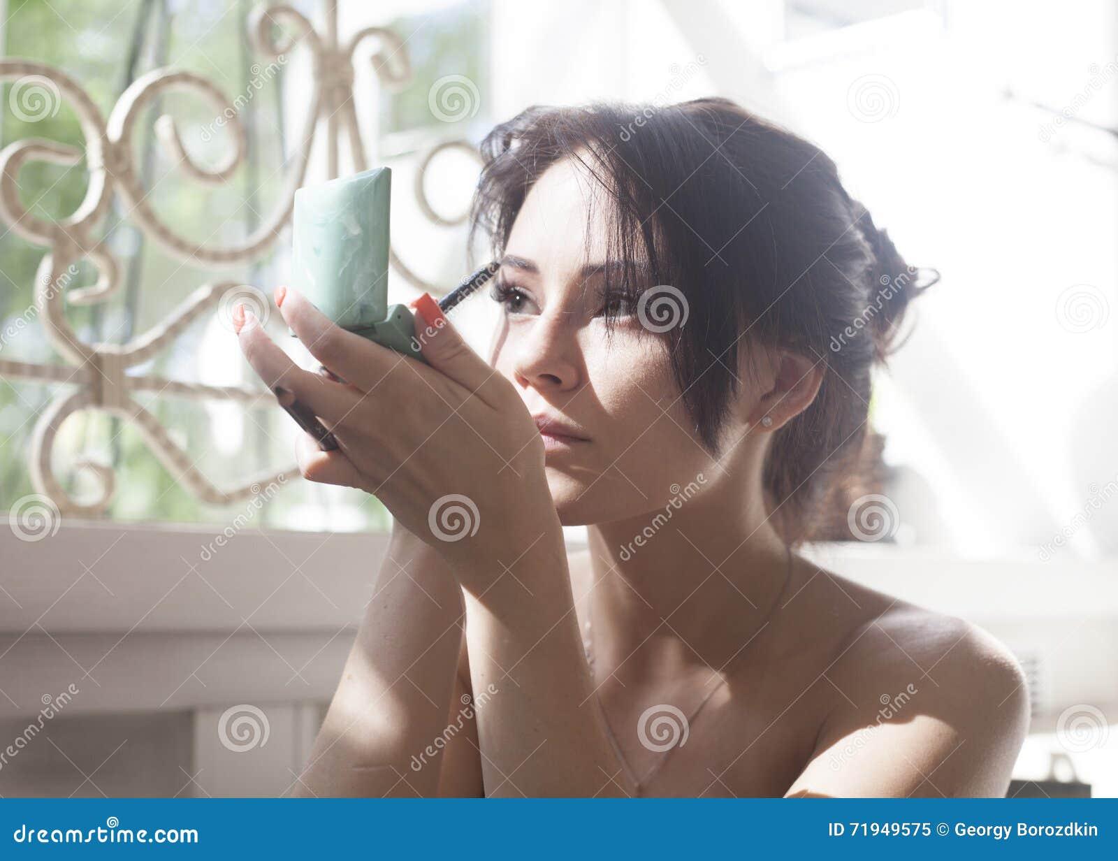 Девушка перед зеркалом для того чтобы приложить состав