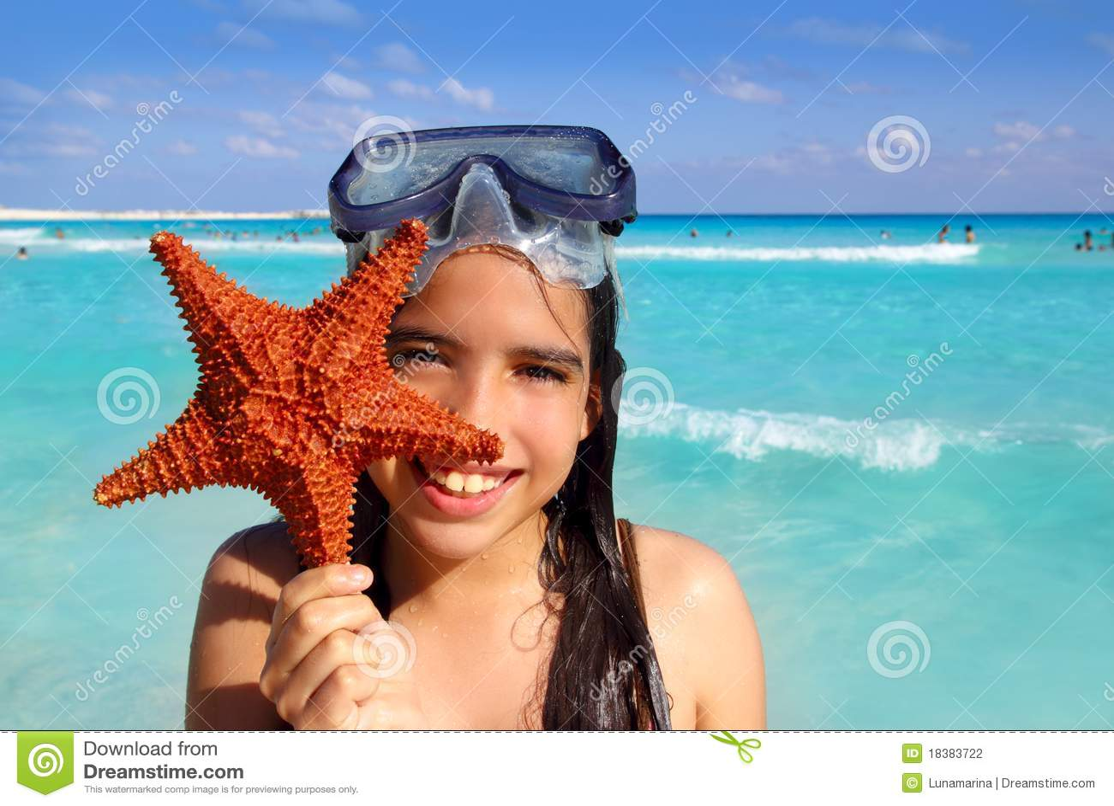 девушка пляжа держа латинского туриста starfish тропическим