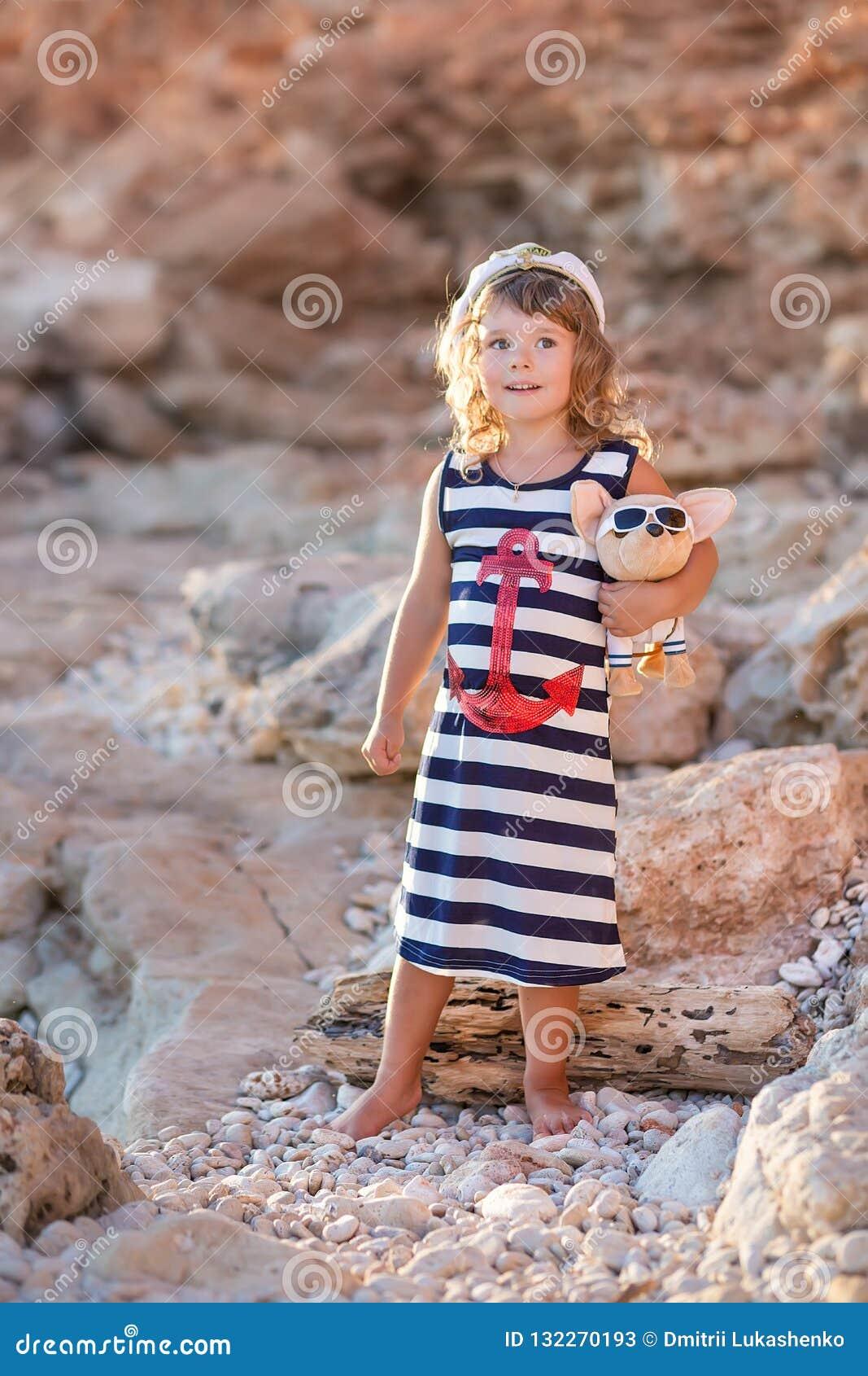 Девушка пляжа милая представляя на скалистом пляже босоногом со стеклами платья и солнца матроса вьющиеся волосы нося